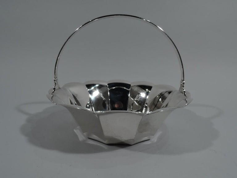 Mid-Century Modern sterling silver basket. Made by Tiffany & Co. in New York. Circular with fluted sides and flared and scalloped rim. Reeded C-scroll swing handle. Hallmark includes pattern no. 23076 and director's letter L (circa