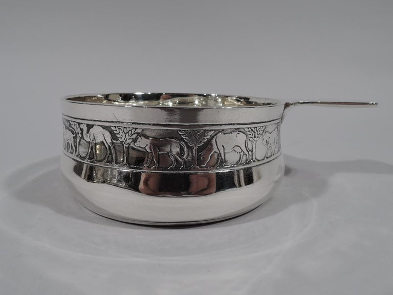Modern sterling silver porringer with Noah's Ark motif. Made by Tiffany & Co. in New York, circa 1926. Gently curved sides and solid shaped handle. On exterior is acid-etched frieze with a lion, camel, elephant, bear—and so on single file through
