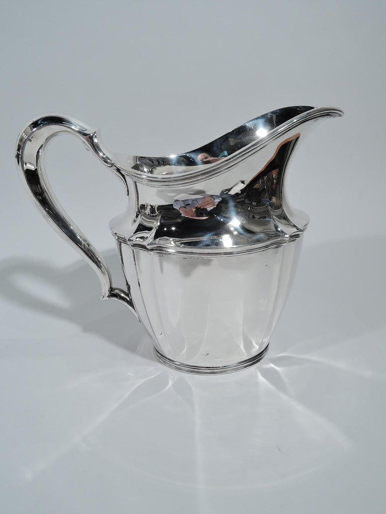 Traditional sterling silver water pitcher. Made by Tiffany & Co. in New York, circa 1910. Tapering oval body, helmet mouth, and high-looping handle. Fluting and reeding. Fully marked including pattern no. 14997D, director's letter m, and volume (3