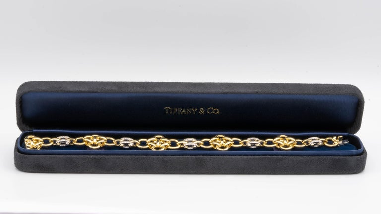 This Tiffany and Co. bracelet is a lot heavier than it looks, and has a very satisfying heft to it. It's finely crafted in 18 Karat gold with Quatrefoil round yellow gold links, spaced by white gold bars. The double row channel style bars are set