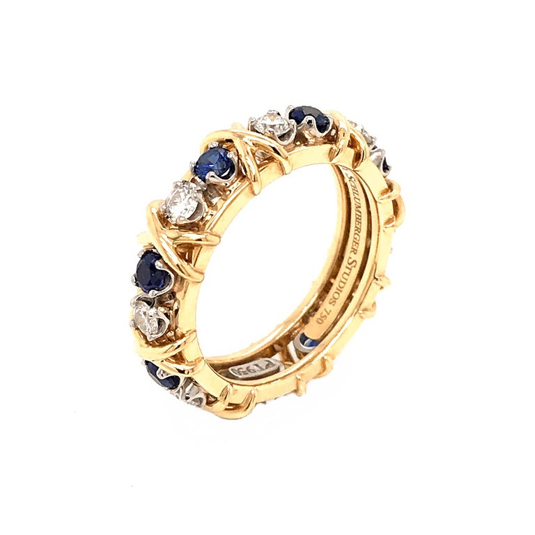 Jean Schlumberger's visionary creations are among the world's most intricate designs. Brilliant sapphires and diamonds alternate with X's, creating this dazzling design.  18K White Gold TOTAL WEIGHT: 9 grams RING SIZE: 7.75 Diamonds = 0.59 ct