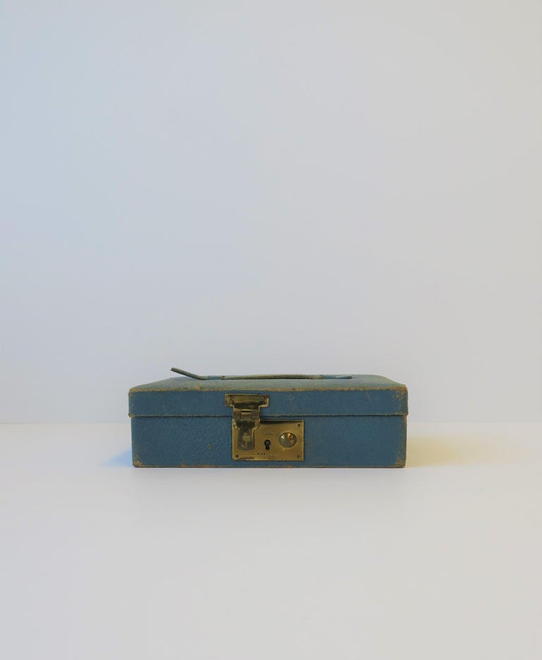 A blue leather, velvet, and brass jewelry box, made in London, circa early-20th century, England. Box is a 'Tiffany' blue leather, with a top handle, brass closure in front, and velvet lined, including a jewelry pillow. Brass closure is marked