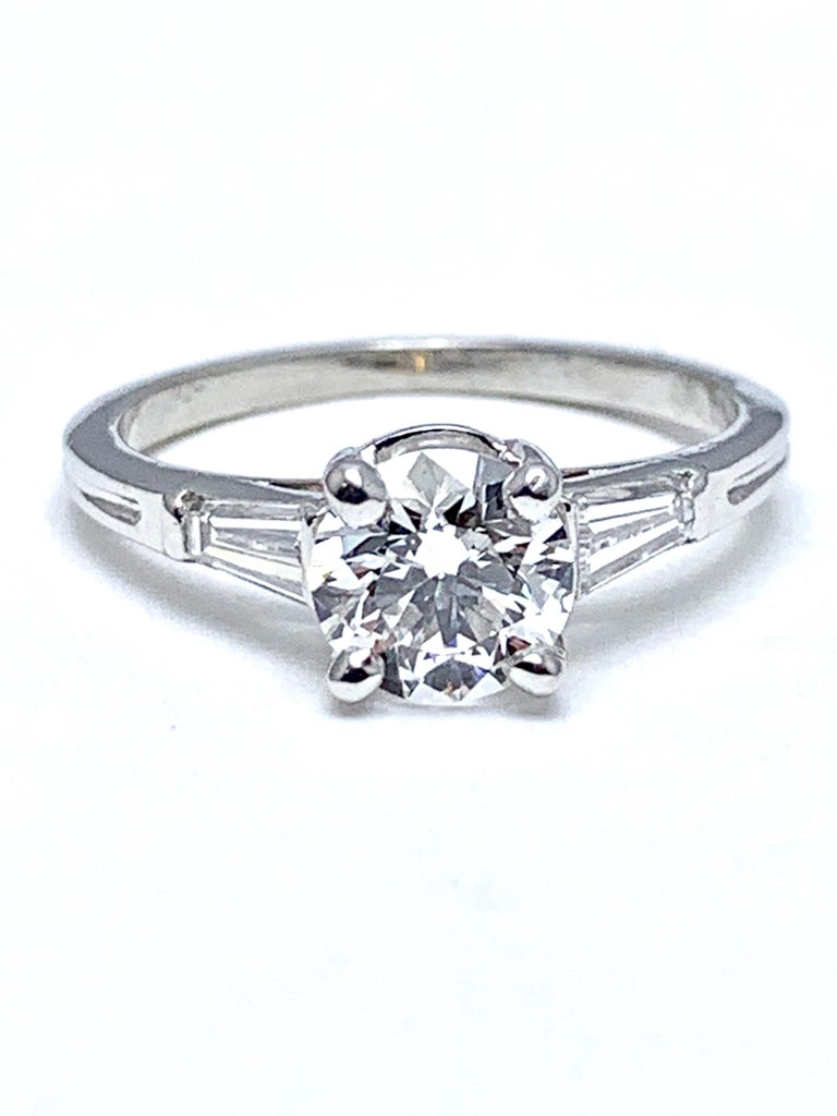 A fiery Tiffany & Co. 1.05 carat round brilliant Diamond and tapered baguette Diamond platinum engagement ring.  The center Diamond is set in a four prong basket setting, with two tapered baguettes leading into the shank of the ring.  The 1.05 carat