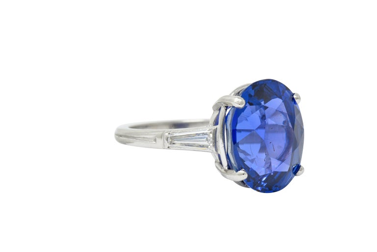 Cathedral basket ring centers an oval cut Ceylon sapphire weighing 11.83 carats  Transparent and intensely violetish-blue in color with no indications of heat; Sri Lankan in origin  Flanked by two tapered baguette cut diamonds weighing approximately