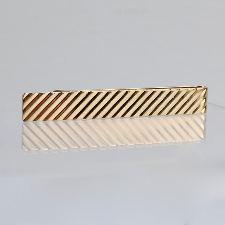 A handsome Tiffany & Co. tie clip in 14K gold.  The tie bar features a repeating diagonal stripe pattern.   Simple and elegant design from Tiffany!  Date: Mid-20th Century  Overall Condition: It is in overall good, as-pictured, used estate condition