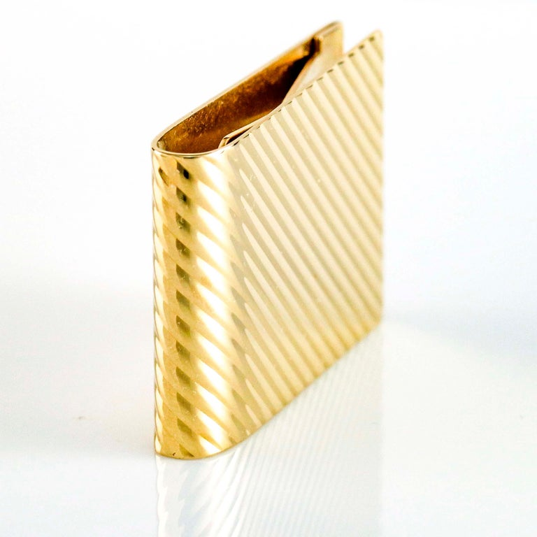 Tiffany and Co. wide money clip in 14 karat yellow gold with groove pattern. Smooth polished metal back.