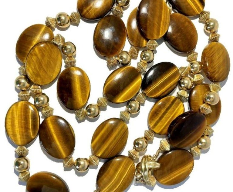 This very pleasing 14k yellow gold Tiffany neck chain is comprised of twenty one natural oval quartz tiger's eye slabs, all separated by sets of three 14k fluted and polished beads.  It features an iconic Tiffany