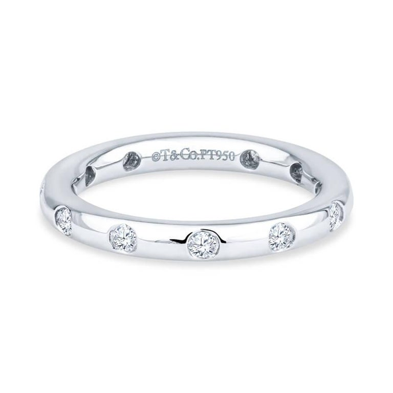 This stylish ring is crafted of platinum and features bezel set diamonds throughout the band with a total approximate carat weight of 0.18. It is size 5 and can be worn as a wedding band or eternity band. The original MSRP is $2,525.   Condition:
