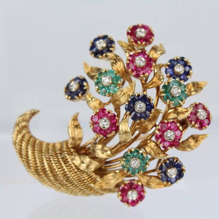 A fine and rare Tiffany & Co. 18-karat yellow gold en tremblant brooch set with diamonds, sapphires, rubies, and emeralds.  Simply exquisite with gemstone rosettes, textured gold leaves, and a wirework cornucopia basket.  Each flower trembling