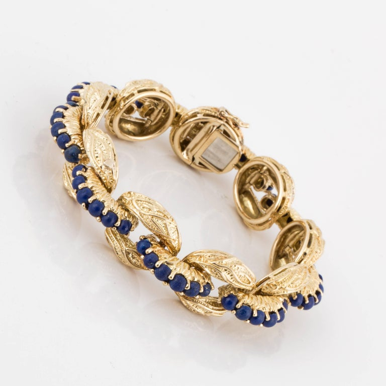 Bracelet made by Tiffany & Co.  Textured 18K yellow gold oval links with Lapis beads down the center adjoining links.  There are a total of forty-seven (47) beads.  Bracelet measures 7-3/8