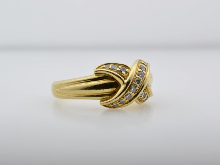This vintage Tiffany & Co. gold and diamond ring is a beautiful modern design- sleek and structured. A crisscross of diamond ( aprox. 0.30 tw) bands hug around a substantial gold ring creating a powerhouse of a statement. Glamorous, chic, and