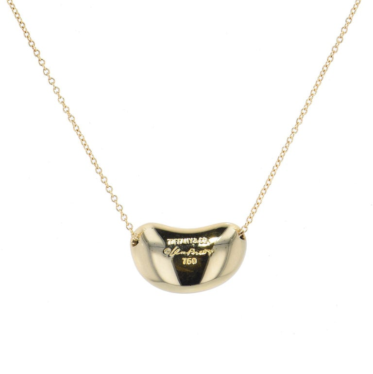 Enjoy this previously loved Tiffany & Co. Elsa Peretti 18 millimeter wide 18 karat yellow gold bean pendant strung on 18 inch yellow gold chain. The bean represents the origin of all things and is a great gift to mark life's special milestones.