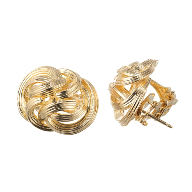 Tiffany & Co 18k yellow gold earrings in a stylized knot design with fluted accents. Pierced earrings with clip backings.  18k yellow gold  Stamped: 750 Hallmark: Tiffany & Co 1.9 Grams Top to Bottom: 23.7mm or 15/16 Inches Width: 17.97mm or 11/16