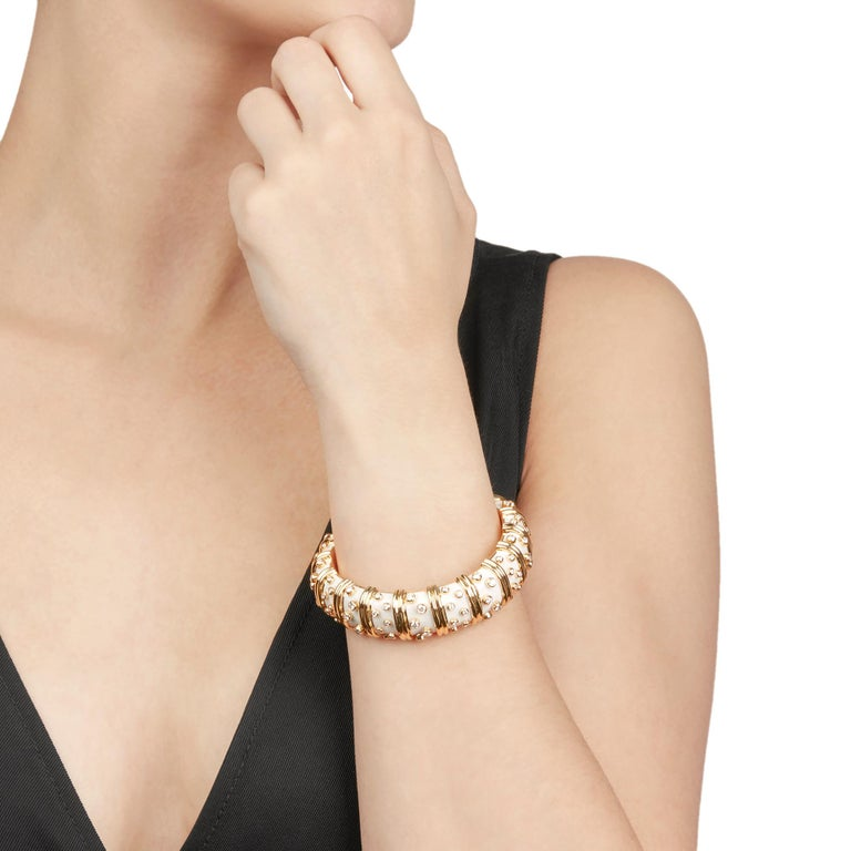 This Bracelet by Tiffany & Co. is from their Schlumberger collection and features white enamel and round brilliant cut Diamonds, mounted in 18k Yellow Gold. The Bracelet has a concealed push button clasp. This Bracelet has recently been polished by
