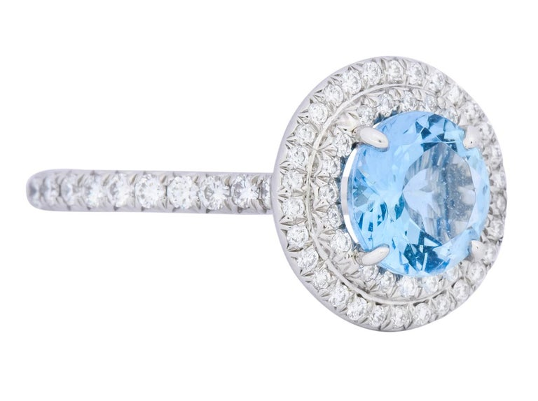 Centering a round cut aquamarine weighing approximately 1.25 carat, transparent medium-dark sea blue in color  Surrounded by a double halo and shoulders bead set with round brilliant cut diamonds weighing approximately 0.60 carat total, F/G color