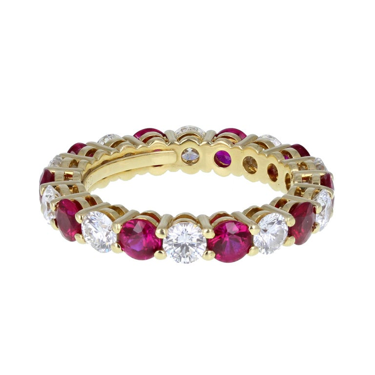 From the iconic jewellery house of Tiffany & Co. an exquisite full hoop ruby and diamond eternity ring in 18-carat yellow gold. Comprising ten brilliant-cut rubies and ten brilliant-cut diamonds, alternating and each mounted in four simple 18-carat