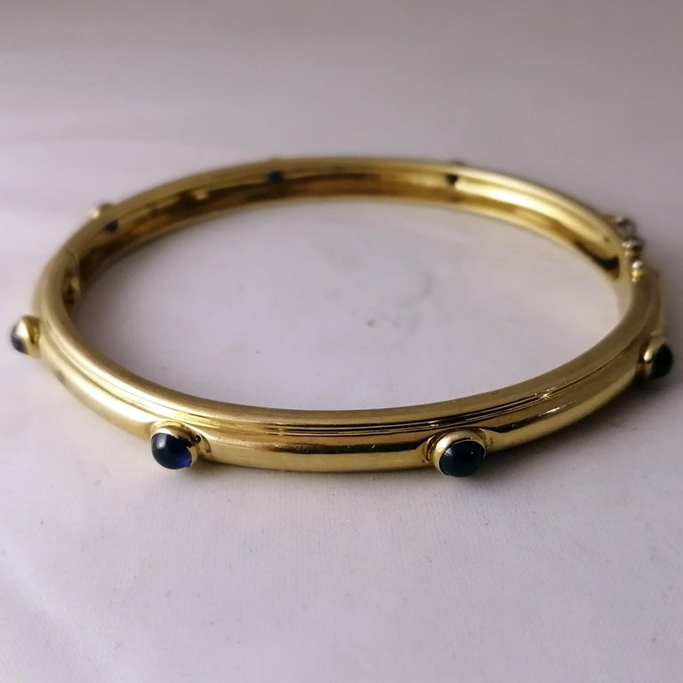 A fabulous Italian made 18-karat gold and sapphires bangle bracelet by Tiffany & Co. The hinged bangle has 8 bezel set cabochon sapphires and safety chain. The piece is marked on the interior with the Tiffany & Co. logo, the 750 mark and the ITALY