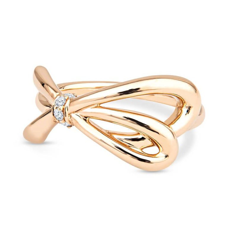 A stylish and fashion forward ring crafted in 18 karat rose gold featuring an asymmetrical cross over bow that is accented at the center with 4 round brilliant diamonds totaling .05 carats. This is currently a size 5.5 but can be resized upon
