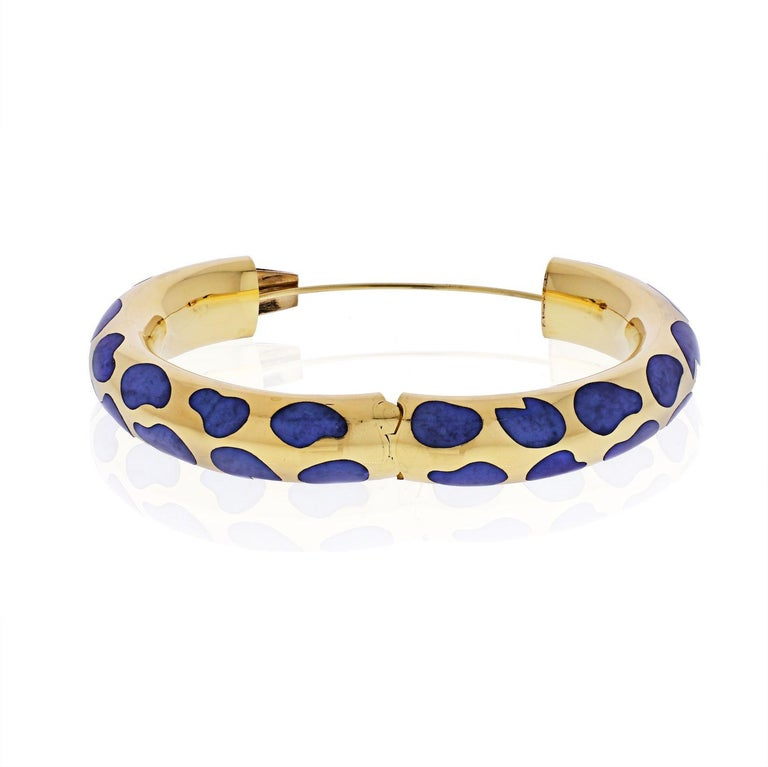 This fabulous Tiffany & Co. bracelet designed by Angela Cummings is crafted in 18k yellow gold and features chic fluid shapes inlaid with lapis lazuli. This bangle was made in United States circa 1980s.  Wrist size 6.5 inches to 6.75in.