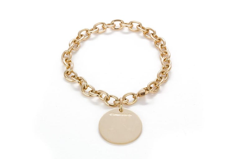 We are pleased to offer this Tiffany & Co. 18k Yellow Gold Round Charm Bracelet. In classic Tiffany style this bracelet is crafted from 18k yellow gold and features a round charm. Streamlined and modern, this bracelet shines with sophistication and