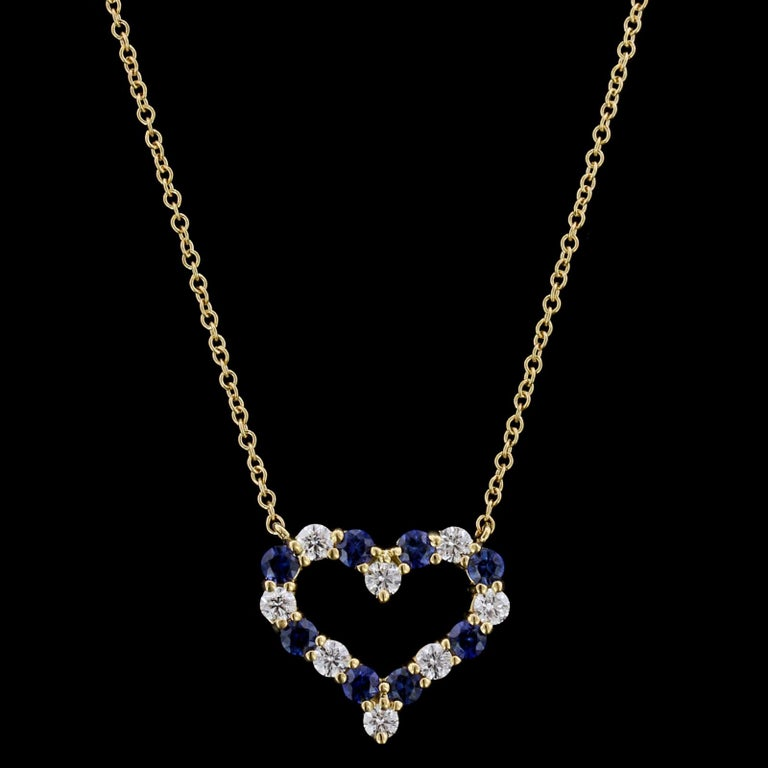 Tiffany & Co. 18K Yellow Gold Sapphire and Diamond Heart Pendant. The pendant is set with eight round cut sapphires, approx. total wt. .55cts., and eight full cut diamonds, approx. total wt. .36cts., F color, VS clarity, length 17