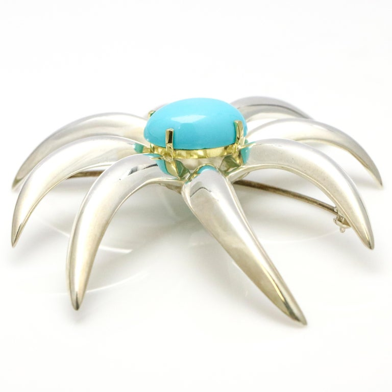 1995 Tiffany & Co. Fireworks Brooch in sterling silver and 18 karat yellow gold. The pin has a cabochon Persian turquoise gemstone center. Turquoise, 16mm x 12mm.