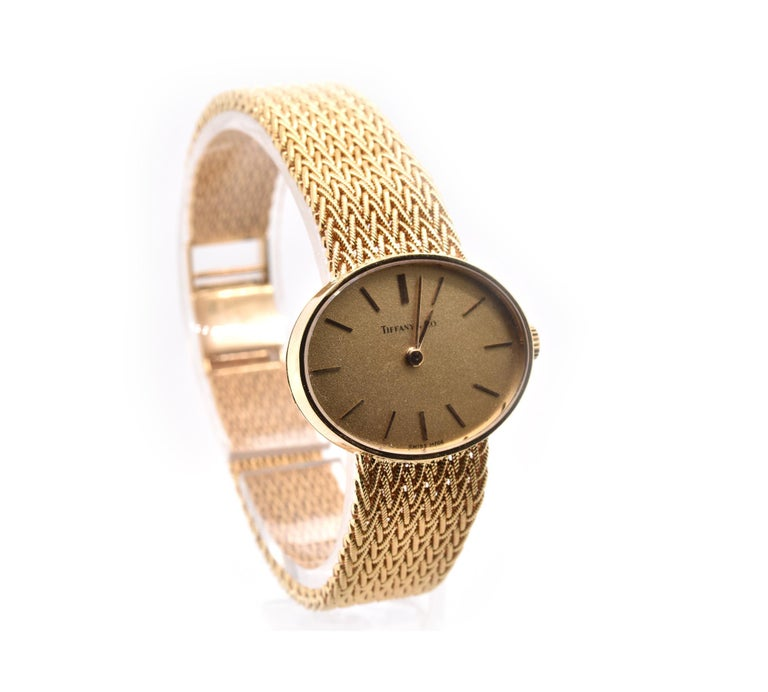 Movement: automatic Function: hours, minutes Case: 26mm x 21mm yellow gold case, sapphire crystal, push/pull crown Band: T&Co yellow gold mesh bracelet with ladder clasp Dial: champagne dial, gold stick hour markers Serial#: 53XXX Reference#: