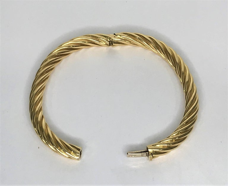 Tiffany & Co. 18 karat gold twist bangle bracelet. 18 karat solid yellow gold  hinged bangle bracelet.   Oval shape to fit wrist.  Twisted design, polished gold, approximately 6.7mm wide. Approximately 7 inch inside circumference. Hidden box clasp-