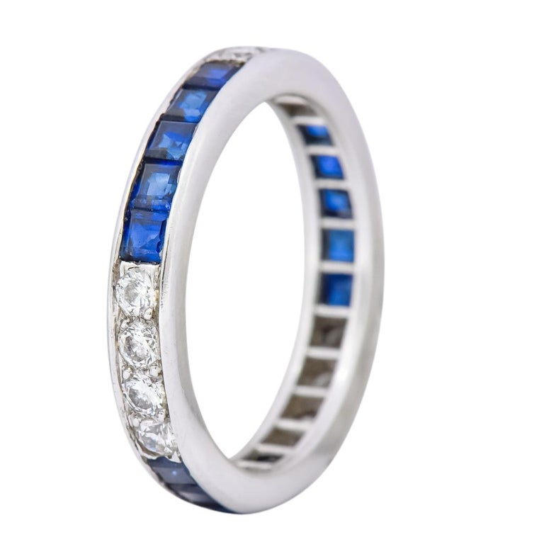 Eternity style band with polished channel edges  Channel set with square cut sapphires weighing approximately 1.00 carat total, inky blue in color and very well matched  Alternating with bead set round brilliant cut diamonds 0.42 carat total, G/H