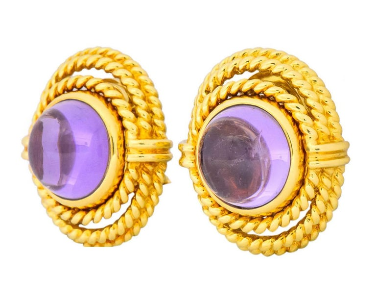 Each centering a round cabochon amethyst measuring approximately 12.0 mm, transparent and light purple in color  Bezel set in gold surmount designed as three coils of rope with ribbed gold detail  Completed by post and hinged omega backs  Fully