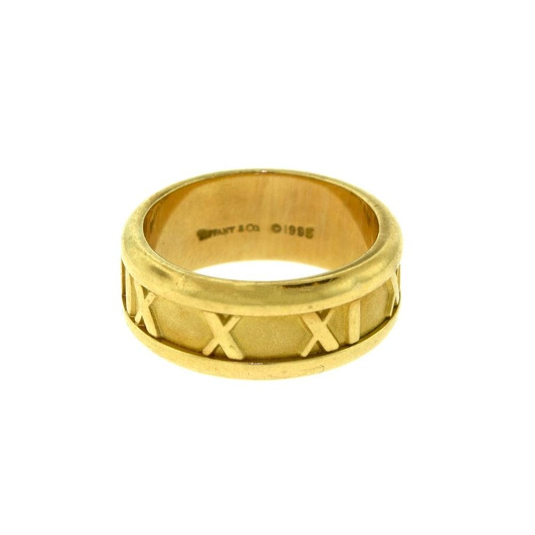 Brilliance Jewels, Miami Questions? Call Us Anytime! 786,482,8100  Ring Size: 4.5  Designer: Tiffany & Co.  Collection: ATLAS  Style: Roman Numerals  Metal: Yellow Gold  Metal Purity: 18k    Total Item