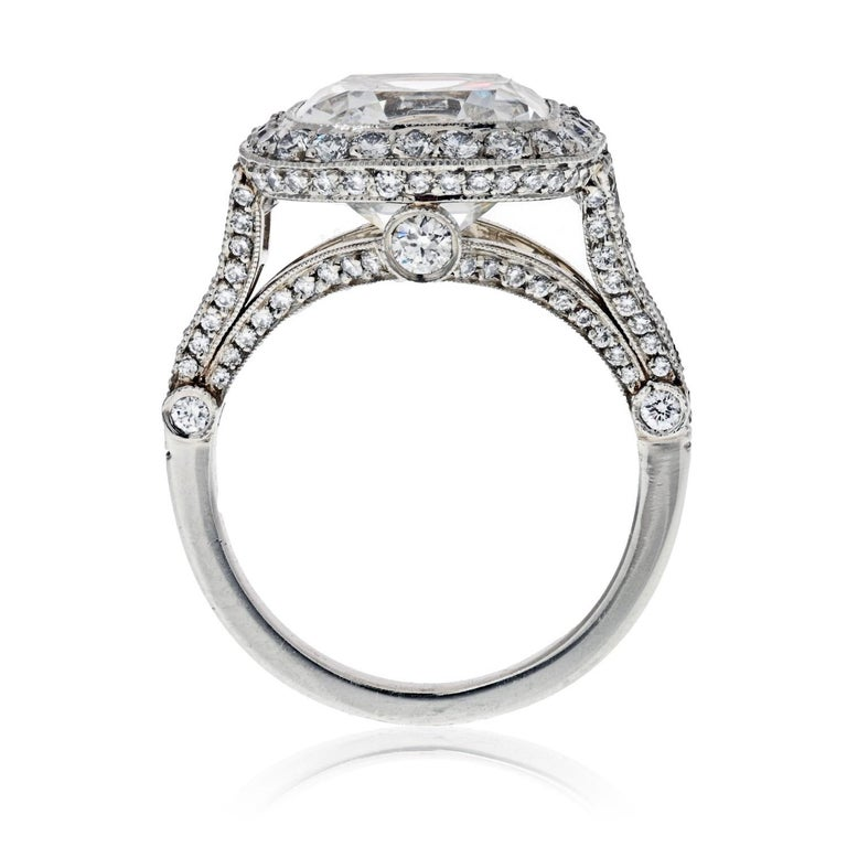 Legacy diamond engagement ring, centering on a cushion-cut diamond weighing 5.56 carats, with a pave diamond surround and basket, as well as five graduated round-cut diamonds at either shoulder and six larger round-cut profile diamonds, the 134