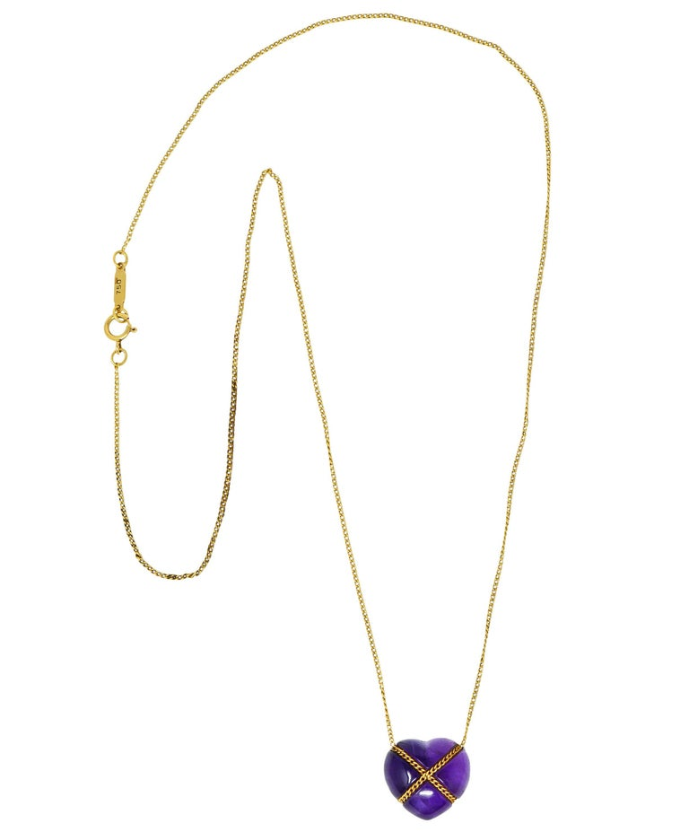 Classic curb chain necklace centers an amethyst heart cabochon  Bright purple and translucent with natural inclusions  Tightly wrapped with curb chain in an X motif  Necklace completes as a spring ring clasp  Logo link is stamped 750 for 18 karat