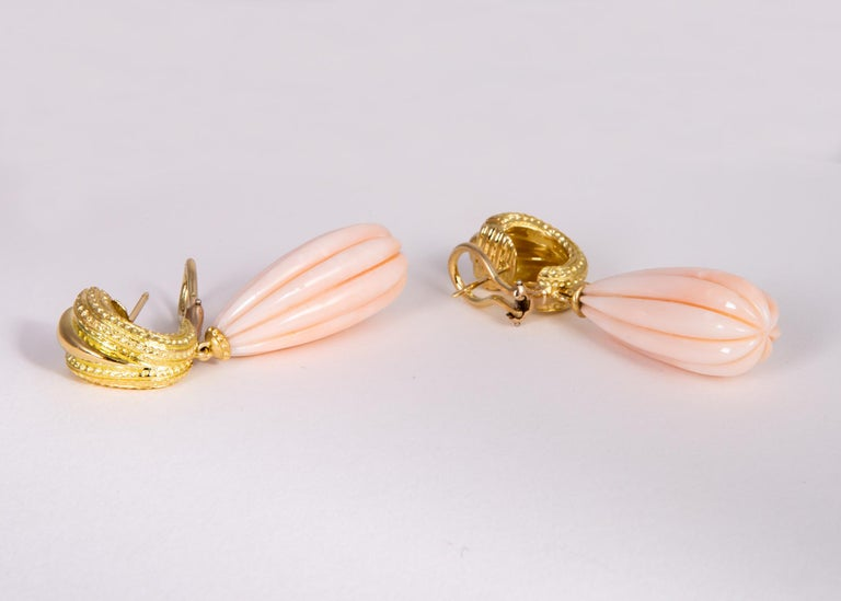 This elegant pair of vintage Tiffany & Co. earrings feature a pair of fluted angel skin coral with rarely seen completely even tone coloration. 2 inches in length.