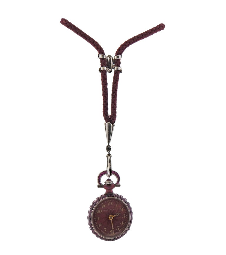 Antique platinum Tiffany & Co pocket watch, suspended on a cord necklace. Case adorned with rubies and diamonds. Case measures 18mm in diamonds. 28