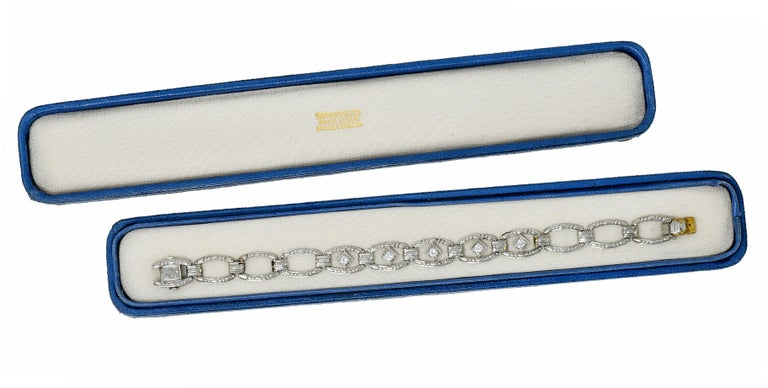 Link style bracelet with elongated rectangular cushion links alternating with spacer links  Featuring a dot and dash motif throughout and a deeply engraved orange blossom at clasp  Links center five navette forms set with transitional cut diamonds