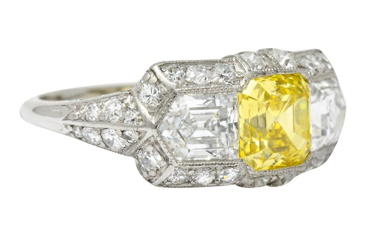 Rectangular mount centers an asscher cut fancy colored diamond weighing 1.43 carats; VS1 clarity and fancy vivid yellow with natural and even color throughout  Flanked by two bullet cut diamonds weighing in total approximately 2.30 carats; D color