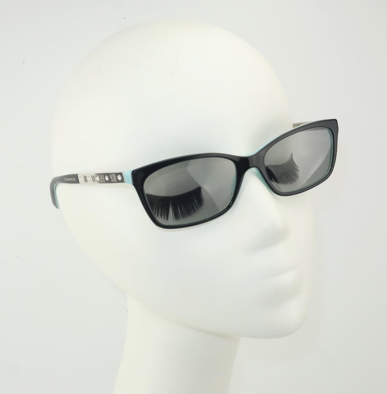 The Italian luxury eyewear brand, Luxotica, creates a classic rectangular frame for Tiffany & Company.  The black frame is lined in Tiffany's signature blue and features silver arms accented by Roman numerals and sparkling crystals.  The gray lenses