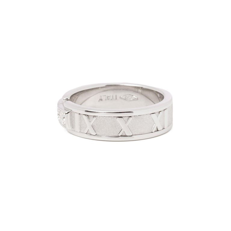 This ring by Tiffany & Co is from their Atlas collection and features 3 round brilliant cut diamonds set within an 18ct white gold band ring. The band features the iconic Roman numeral design accentuated by the contrast of highly polished and