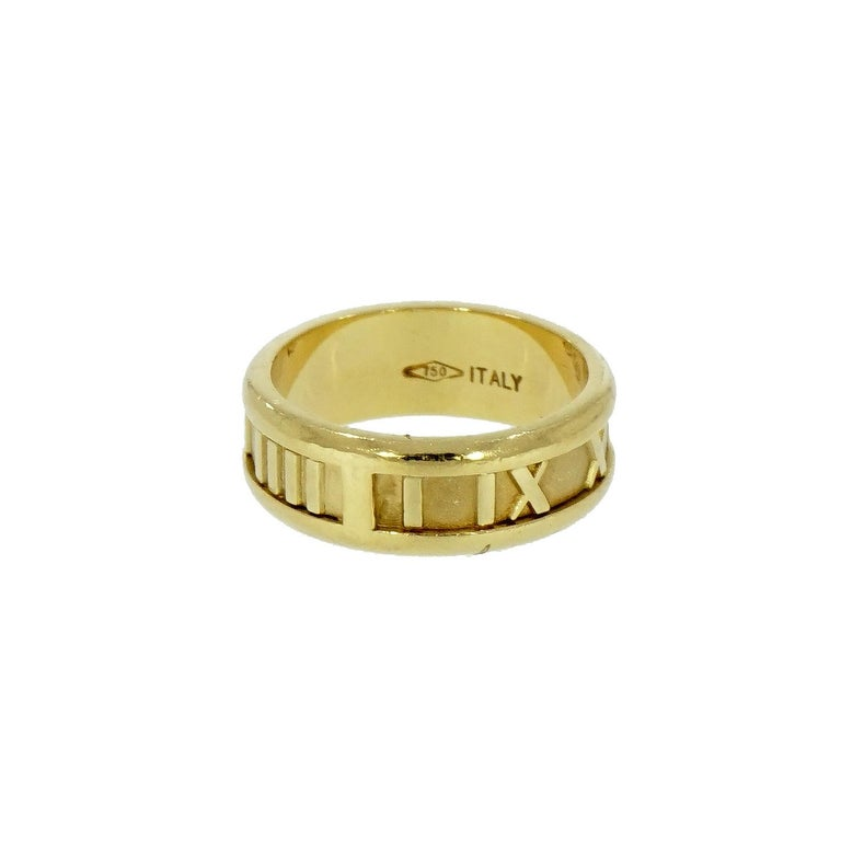 Featuring a wide 18 karat gold band ring from the Atlas Collection by Tiffany & Co. With Roman numerals and borders in highly polished gold, matte finish on lightly textured background Fully signed Tiffany & Co. 1995 Italy 750 (for 18 karat