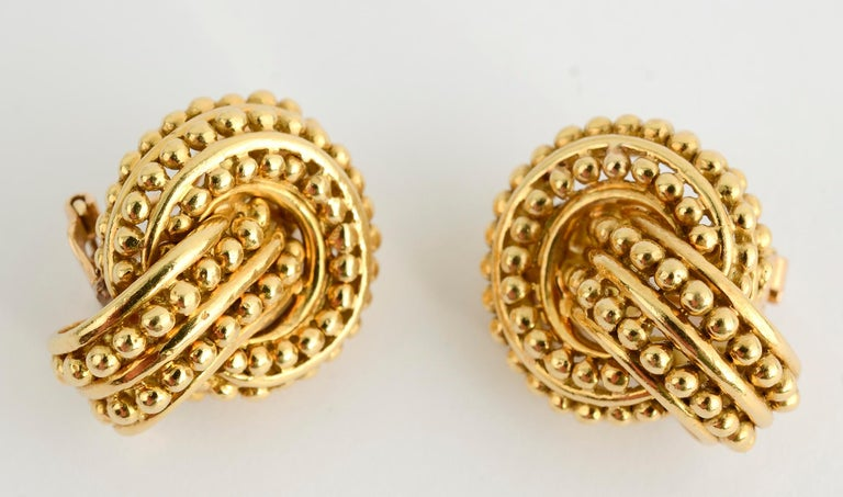 Wonderfully textured and sculptural earrings by Tiffany. An oval half hoop, set on a slight angle, intertwines with a gold circle. Three rows of gold beading are on the circle and two rows on the oval. The earrings measure 1 inch long and 3/4 inch