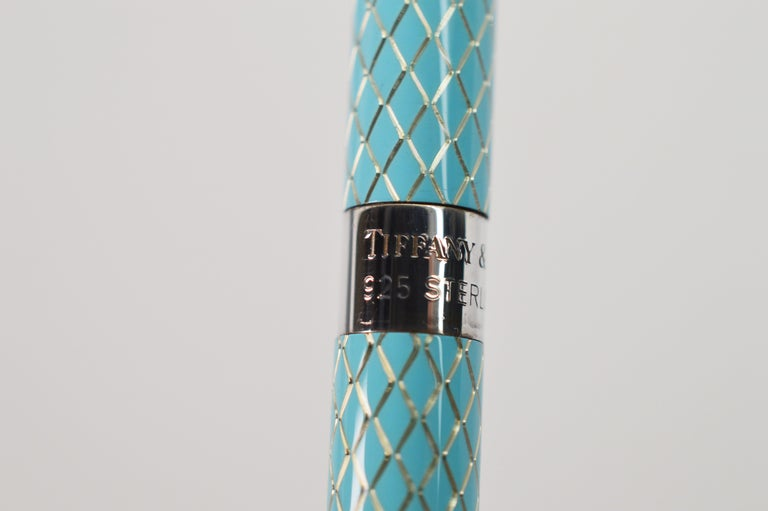 Write in style with this slimline Tiffany & Co. Ladies Ball Point Pen with diamond pattern enamel on silver. Retractable ball point. With original Tiffany pouch and box.