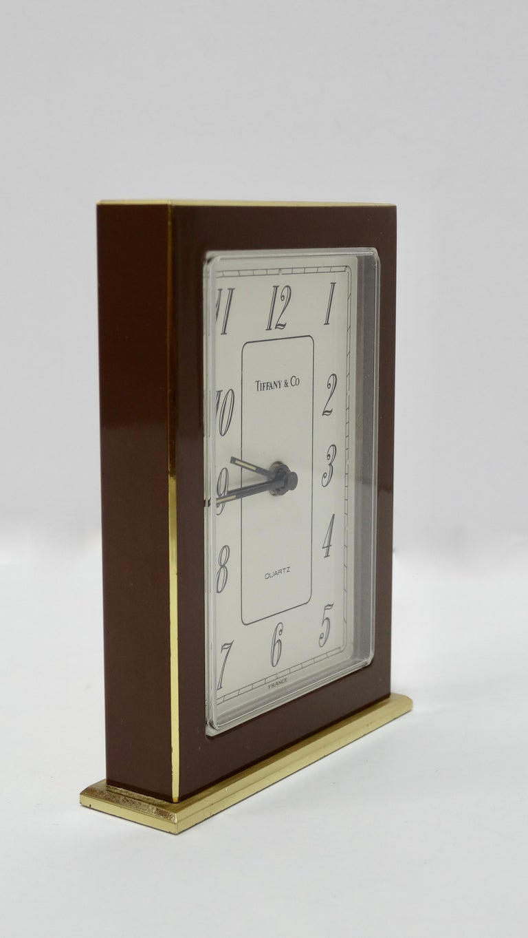 Elevate your desk with this Tiffany & Co. clock! Circa 1960s and made in France, this simple art deco brass desk clock is a slim rectangular shape quartz movement and features brown enamel with a white face and black numbers for a clean and timeless