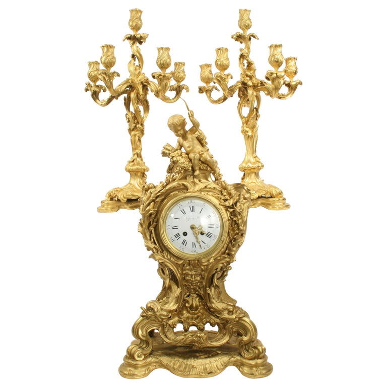 This impressive example of an early 20th century French Rococo palace size clock set comes from the prestigious E. Colin & Cie of Paris foundry. The sculpted ensemble is detailed with crisp elaborate scrolling accented with a full figure cupid with