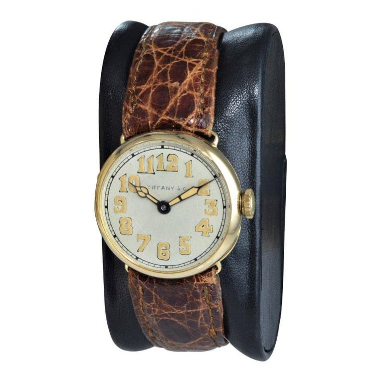 FACTORY / HOUSE: Tiffany & Co. by Longines Watch Company STYLE / REFERENCE: Campaign Style / Art Deco  METAL / MATERIAL: 18KT Yellow Gold CIRCA / YEAR: 1917 DIMENSIONS / SIZE: 27mm X 28mm MOVEMENT / CALIBER: Manual Winding / 15 Jewels  DIAL / HANDS: