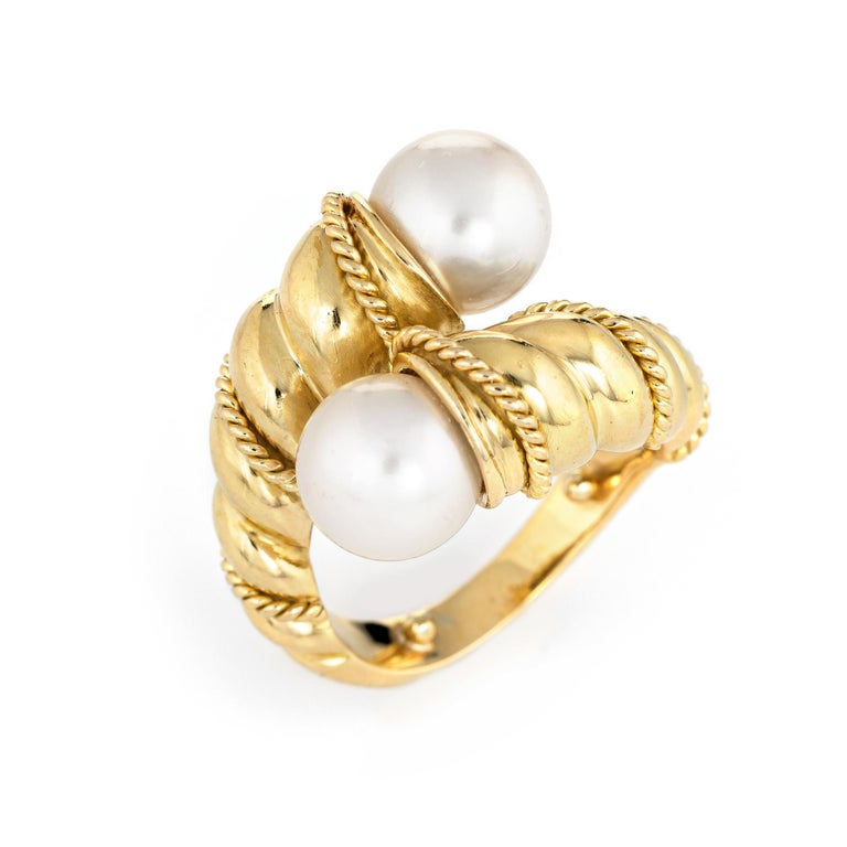 Finely detailed vintage Tiffany & Co cultured pearl bypass ring (circa 1990s) crafted in 18 karat yellow gold.   Two cultured pearls each measure 8mm. The pearls are lustrous and show rose overtones.    The stylish ring features a bypass design with