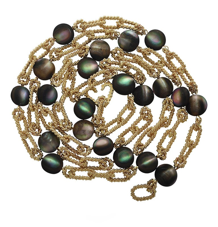 From the iconic House of Tiffany & Co. this vintage necklace, crafted in 18 karat yellow gold, features 21 sensational Cat's Eye Labradorite cabochons. The necklace is fashioned from twisted yellow gold links interspersed with cat's eye labradorite