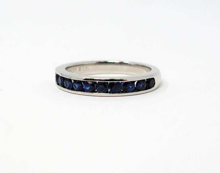 Ring size: 5  Stunning Tiffany & Co. sapphire semi eternity band ring. This timeless beauty features brilliant blue sapphires channel set in a single elegant row. The sleek polished band has a modern, yet feminine feel. It would be stunning paired