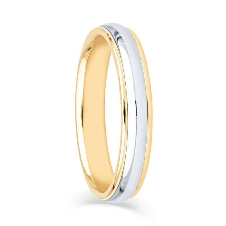 A sophisticated and beautiful wedding band crafted from Platinum and 18k yellow gold. The center features a high polished platinum dome complemented by the 18k yellow gold double edge and a smooth polished finish. The hallmark states Tiffany & Co.