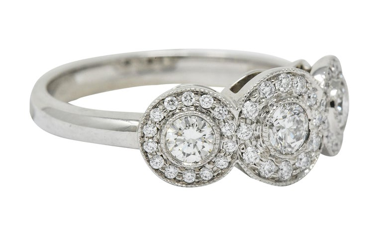 Band style ring is comprised of three circles, each centering a bezel set round brilliant cut diamond  Center diamonds weigh in total approximately 0.50 carat with H/I color and VS clarity  Each surrounded by a circular halo of round brilliant cut